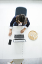 Businesswoman sitting at desk in the office working on laptop, top view - MOEF00497