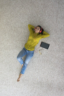 Smiling young woman lying on the floor with headphones and tablet listening music, top view - MOEF00506