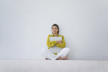Portrait of smiling woman with oversized book sitting on the floor - MOEF00515