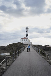 Spain, Menorca, Bernese mountain dog walking together with his owner outdoors at lighthouse - IGGF00288