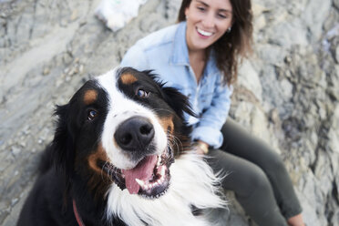Happy bernese mountain dog looking at camera, his owner smiles next to him - IGGF00291