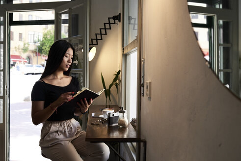 Pretty asian brunette reading a book in a coffee shop next to the window - IGGF00297