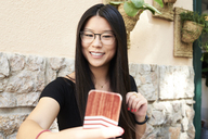 Asian young woman taking a selfie with her smartphone - IGGF00303