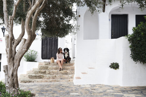 Spain, Menorca, Bernese mountain dog sitted next to his owner in a small white village in summer - IGGF00305