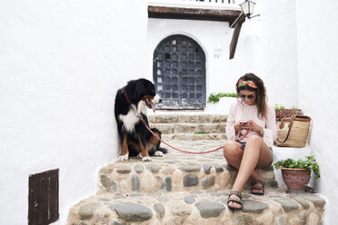 Smiley brunette girl chatting with phone while holding dog lead of her bernese dog in summer - IGGF00308