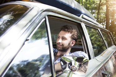 Smiling young man in car in forest - FKF02790
