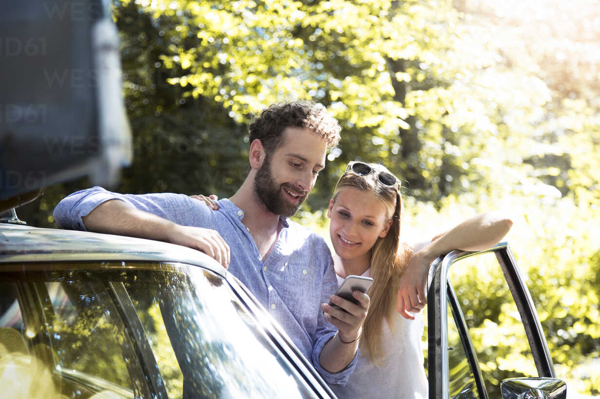 Smiling young couple with cell phone at car in forest - FKF02793 - Florian Küttler/Westend61
