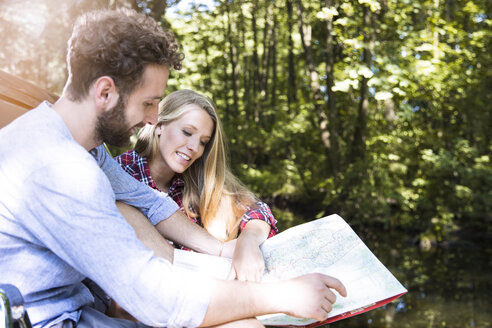 Smiling young couple reading map at a brook - FKF02796