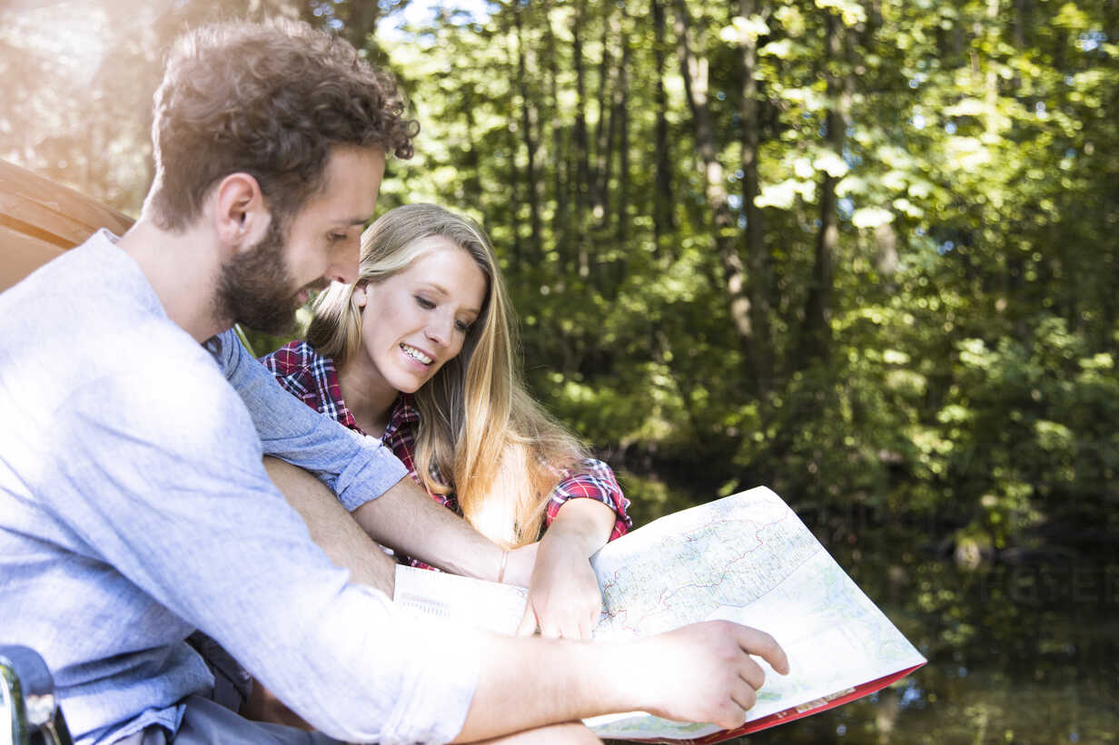Smiling young couple reading map at a brook - FKF02796 - Florian Küttler/Westend61