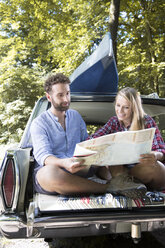 Smiling young couple with map and canoe in car at a brook - FKF02799