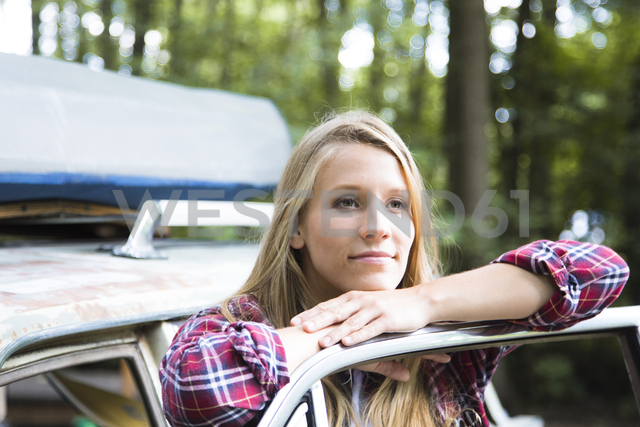 Smiling young woman at car in forest - FKF02802 - Florian Küttler/Westend61