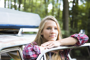 Smiling young woman at car in forest - FKF02802