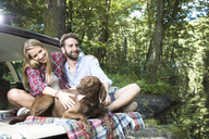Smiling young couple with dog sitting in car at a brook in forest - FKF02805