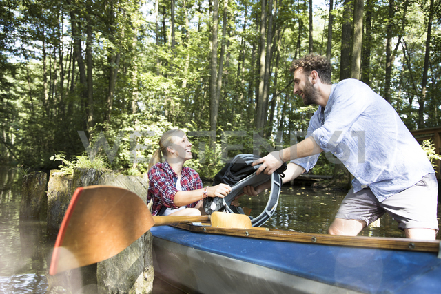 Happy young couple entering canoe in a forest brook - FKF02808