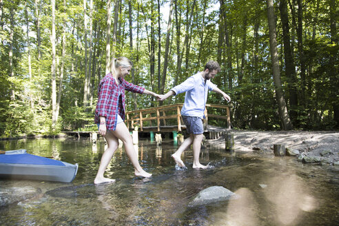 Young couple crossing a forest brook - FKF02811