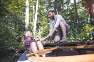 Smiling young man helping girlfriend getting out of a canoe in a forest brook - FKF02814