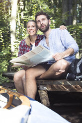 Young couple with map and canoe sitting on a jetty at a forest brook - FKF02817