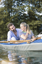 Happy young couple enjoying a canoe trip - FKF02820