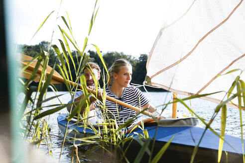 Young couple enjoying a trip in a canoe with sail on a lake - FKF02823