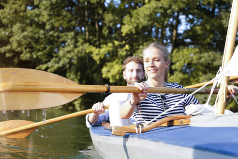 Young couple enjoying a trip in a canoe on a lake - FKF02826