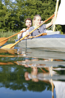 Young couple enjoying a trip in a canoe with sail on a lake - FKF02829