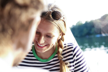 Smiling young woman with man at a lake - FKF02838