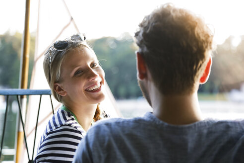 Young woman laughing at man at a lake next to sailing boat - FKF02841