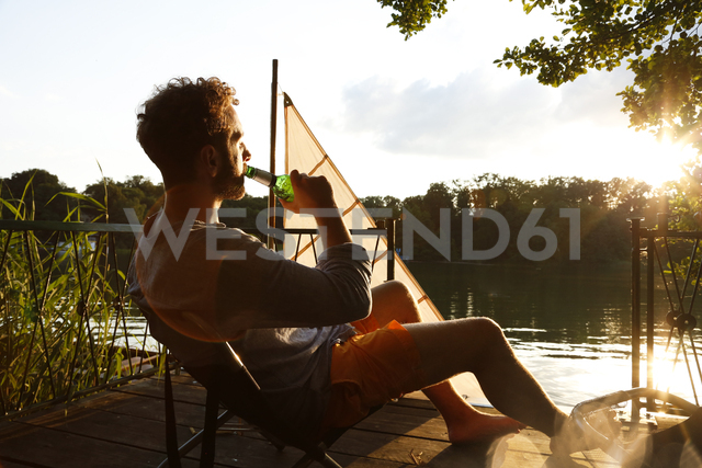 Young man with drinking a beer on a jetty next to sailing boat - FKF02847