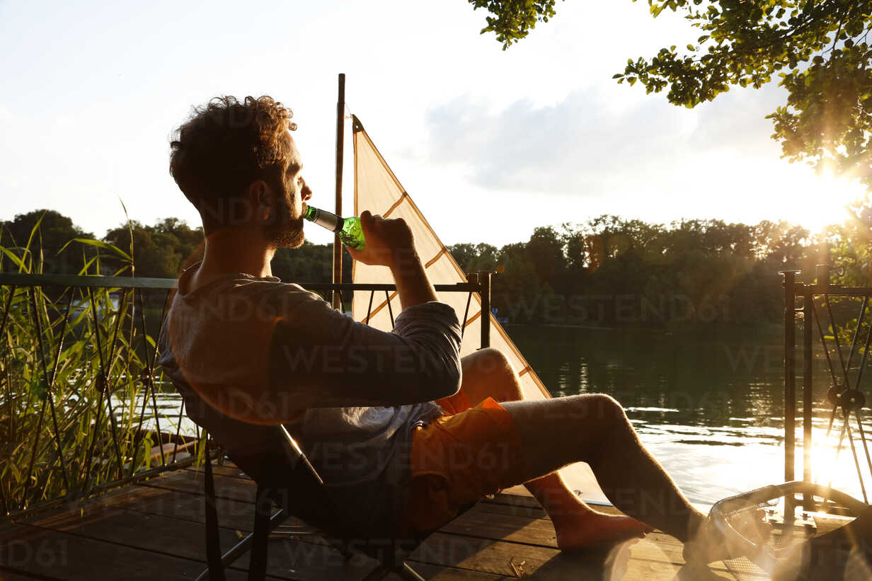 Young man with drinking a beer on a jetty next to sailing boat - FKF02847 - Florian Küttler/Westend61