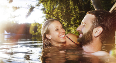 Happy young couple in a lake - FKF02850
