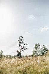 Young man lifting up his bike - GUSF00270