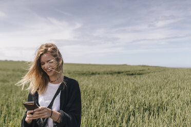 Young woman using smartphone, standing in field - GUSF00294