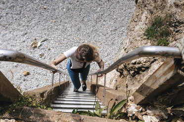 Young woman climbing stairs at the beach - GUSF00297