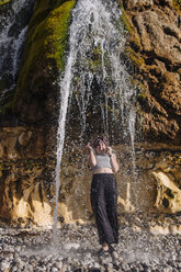 France, Seine-Maritime, Cote d'Albatre, chalk cliff, young woman standing under waterfall at beach - GUSF00303