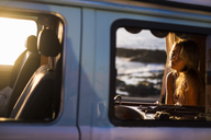 Spain, Tenerife, Blonde girl sitting in a  van at sunset - SIPF01879
