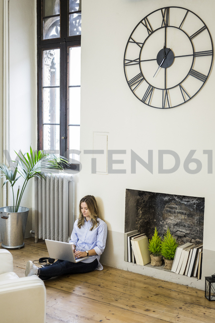 Woman sitting on the floor at home using laptop - GIOF03601