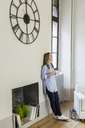 Smiling woman leaning against the wall under clock at home - GIOF03607