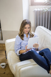 Smiling woman on couch at home holding tablet - GIOF03610