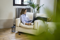 Smiling woman on couch at home using laptop - GIOF03613