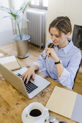 Woman using laptop on wooden desk at home - GIOF03631