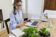 Woman using cell phone and laptop on wooden desk at home - GIOF03634