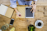 Top view of woman at wooden desk with notebook, cell phone and tablet - GIOF03637