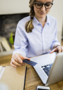 Close-up of woman at wooden desk with card and laptop - GIOF03643