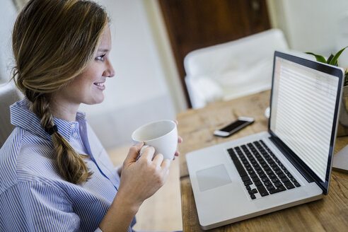 Smiling woman sitting at desk with cup of coffee and laptop - GIOF03646