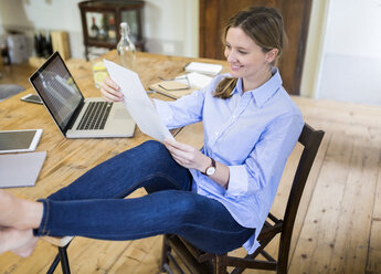 Smiling woman sitting at desk at home with feet up reading document - GIOF03655