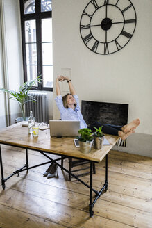 Relaxed woman sitting at desk at home with feet up - GIOF03658