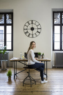 Portrait of smiling woman sitting at desk at home under large wall clock - GIOF03664
