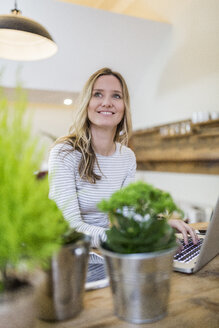 Smiling woman using laptop on wooden table at home - GIOF03667