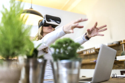 Woman with VR glasses and laptop at home - GIOF03670