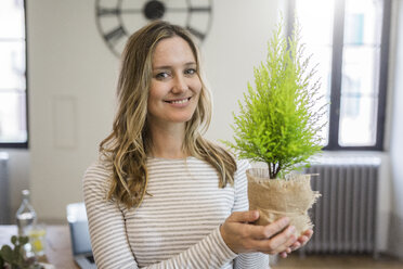 Portrait of smiling woman holding plant at home - GIOF03673